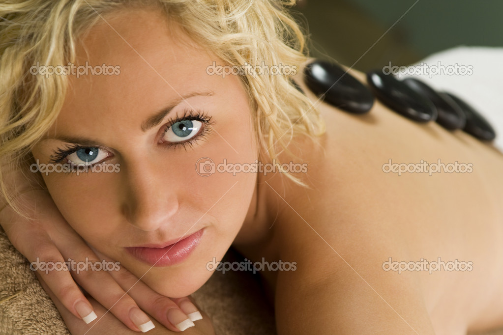 A beautiful young blond woman happily smiles for the camera as see receives a hot stone massage  Stock Photo #6485210
