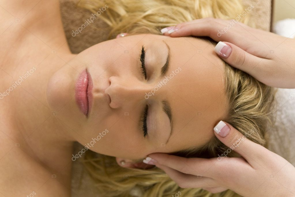 A young blond woman recieving a relaxing head massage from a beauty therapist — Stock Photo #6485224