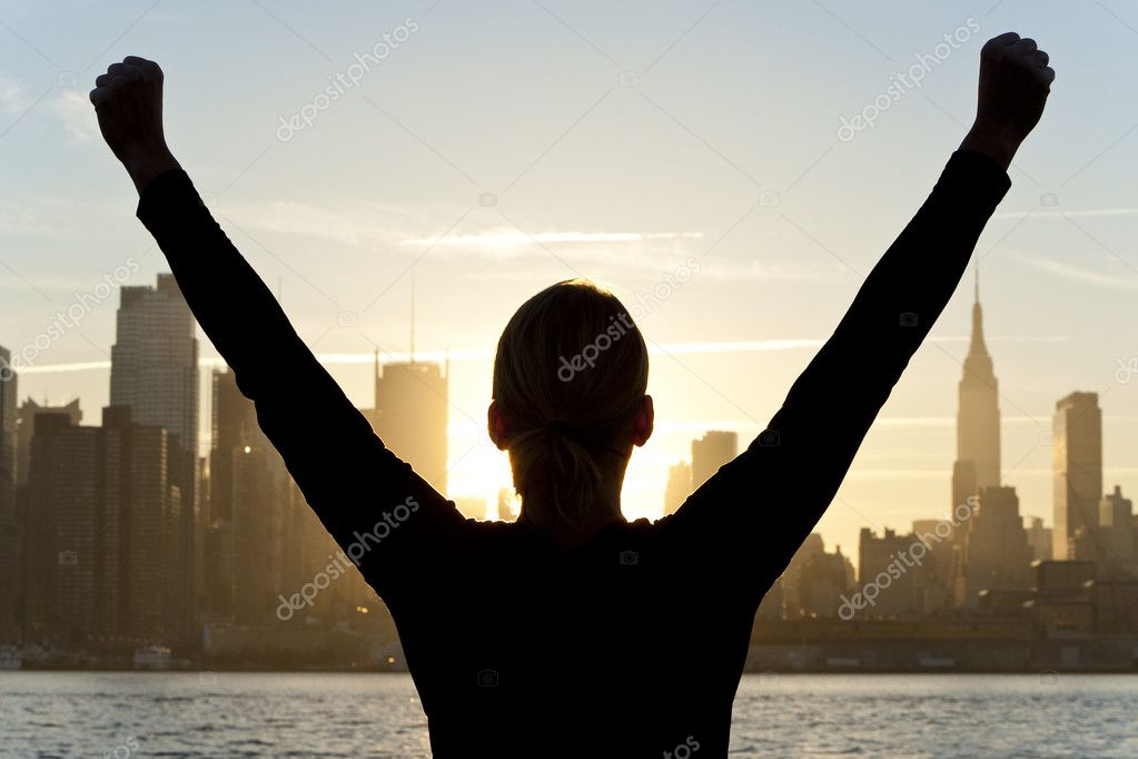 Rear view silhouette of a woman celebrating arms raised at sunrise in front of the Manhattan skyline New York City, United States of America — Stock Photo #6485967