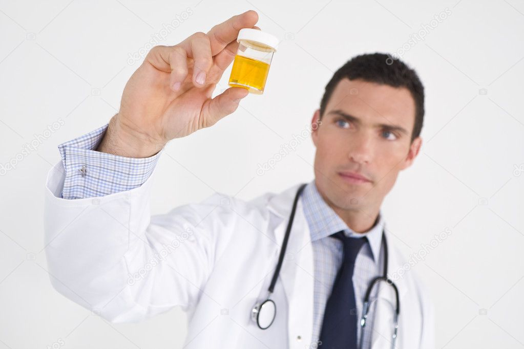 A male doctor examining a urine sample. The focus is on the sample bottle. — Stock Photo #6486734