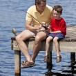 Stock Photo: Father Fishing With His Son On A Jetty