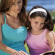 Stock Photo: Woman and Girl, Mother and Daughter, Reading a Book Together Out