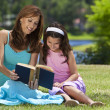 Foto Stock: Woman and Girl, Mother and Daughter, Reading a Book Together Out