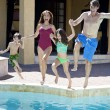 Stock Photo: Family With Two Children Having Fun Jumping Into Swimming Pool