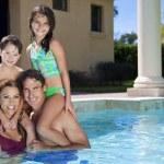 Счастливая семья с двумя детьми, игры в бассейне — Стоковое фото