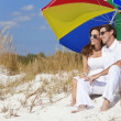 Man & Woman Couple Under Colorful Umbrella on Beach — Stock Photo