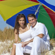 Man & Woman Couple Under Multi Colored Umbrella on Beach — Stock Photo