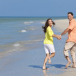 Happy Couple Running Holding Hands on A Beach — Stock Photo #6673323