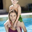 Mother With Son On Her Shoulders In Swimming Pool — Stock Photo #6673347