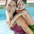 Mother With Son On Her Shoulders In Swimming Pool — Stock Photo