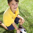 Young Boy Outside Playing With Football or Soccer Ball - Stock Photo