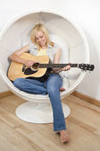 Beautiful Young Blond Woman Playing Guitar in Bubble Chair — Stock Photo