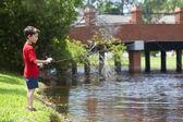 Giovane ragazzo pesca su un fiume — Foto Stock