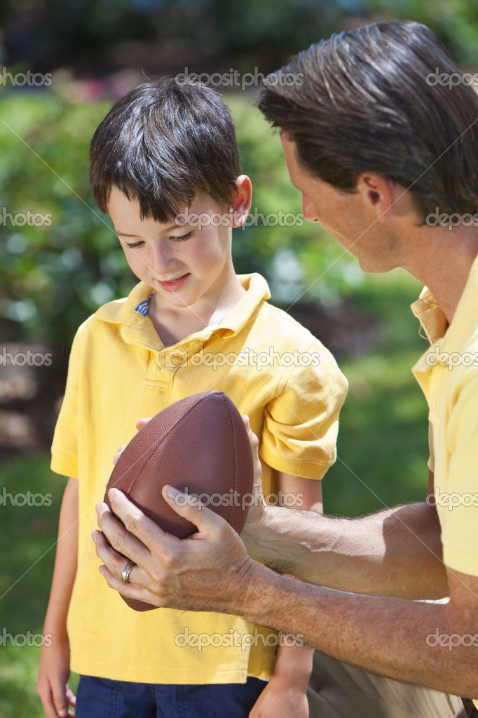 A father teaching his son how to play american football outside in sunshine — Stock Photo #6673353