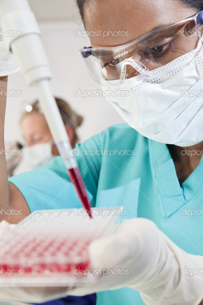 A female Asian medical or scientific researcher or doctor using a pipette and sample tray to test blood sample in a laboratory with her blond female colleague o — Stock Photo #6674000
