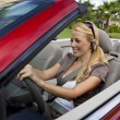Beautiful Young Woman Driving Convertible Car Talking on Bluetoo - Stock Photo