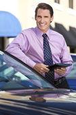 Zakenman leunend op auto met tablet pc — Stockfoto