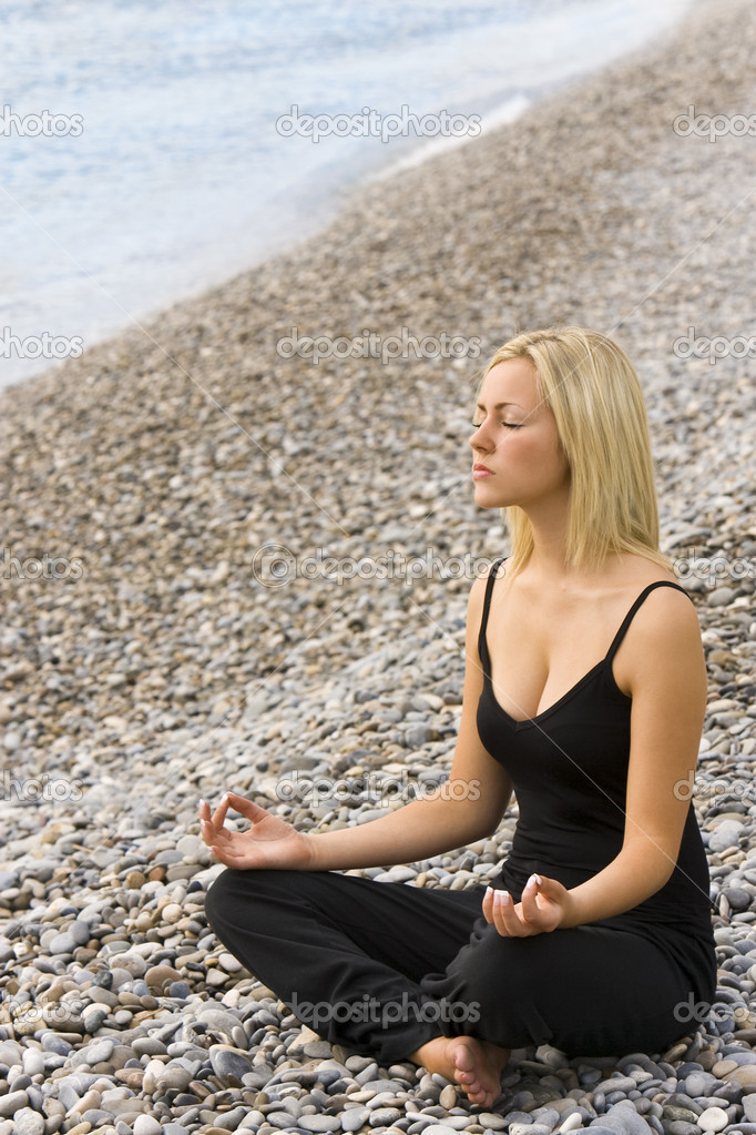 A beautiful young blond woman sitting cross legged in a yoga position on a beach at  — Stock Photo #6685079