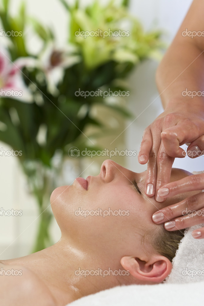 A young woman relaxing at a health spa while having a facial treatment — Stock Photo #6685475