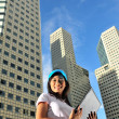 Asihealthy girl smiling sweetly in front of office buildings — Stock Photo #6366622