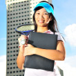 Asian healthy girl holding a tennis racket outdoors — Stock Photo