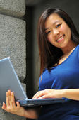 Asian Lady carrying a laptop smiling — Stock Photo