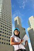 Asian healthy girl smiling sweetly in front of office buildings — Stock Photo