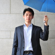 Asian Young Man with blue umbrella indoors — Stock Photo