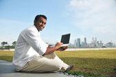 Kostým Indián tvrdě pracuje na jeho laptopu — Stock fotografie