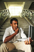 Indian Man with laptop sitting at the stair case — Stock Photo