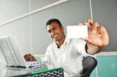 Indian Man holding up a name card — Stockfoto