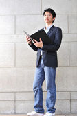 Asian Student with a file looking enthusiastic — Stockfoto
