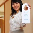 Asian woman holding up hotel signage — Stock Photo