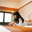 Beautiful chinese office lady working in her hotel room — Stock Photo