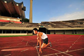 Asian Chinese man preparing his run at the stadium — Stock Photo