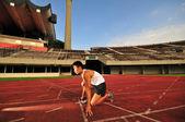 Asian Chinese man preparing his run at the stadium — Stock Photo