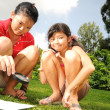 Two children playing with a science experiment outdoors — Stock Photo