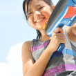 Asian chinese young girl playing with a water gun — Stock Photo