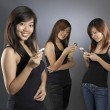 Asichinese girls group using their mobile phones — Stock Photo #6547520