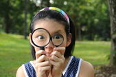 Chinese girl playing detective with magnifying glass — Stock Photo