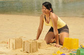 Asian Chinese Girl making sandcastle along the beach — Stock Photo