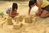 Asian chinese girls playing in the sand — Stock Photo