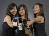 Asian chinese girls group using their mobile phones — Stock Photo