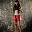 Asian chinese thai girl in muay thai pose and textured background — Stock Photo