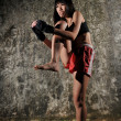 Stock Photo: Asian chinese thai girl in muay thai pose and textured background