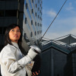Asian chinese female fencer in the city — Stock Photo