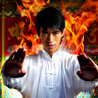 Royalty-Free Stock Photo: Asian Chinese Man in flames emerging at high point of kung fu