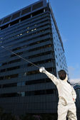 Fencer in the city background — Stock Photo