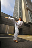 Asian chinese lady in karate gear in the city district — Stock Photo