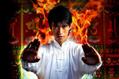 Asian Chinese Man in flames emerging at high point of kung fu — Stock Photo